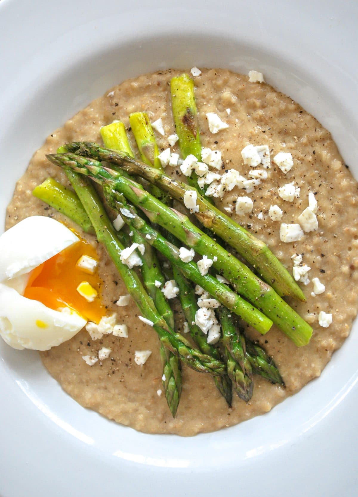 A bowl of Soft Boiled and and Asparagus on steel cut oats