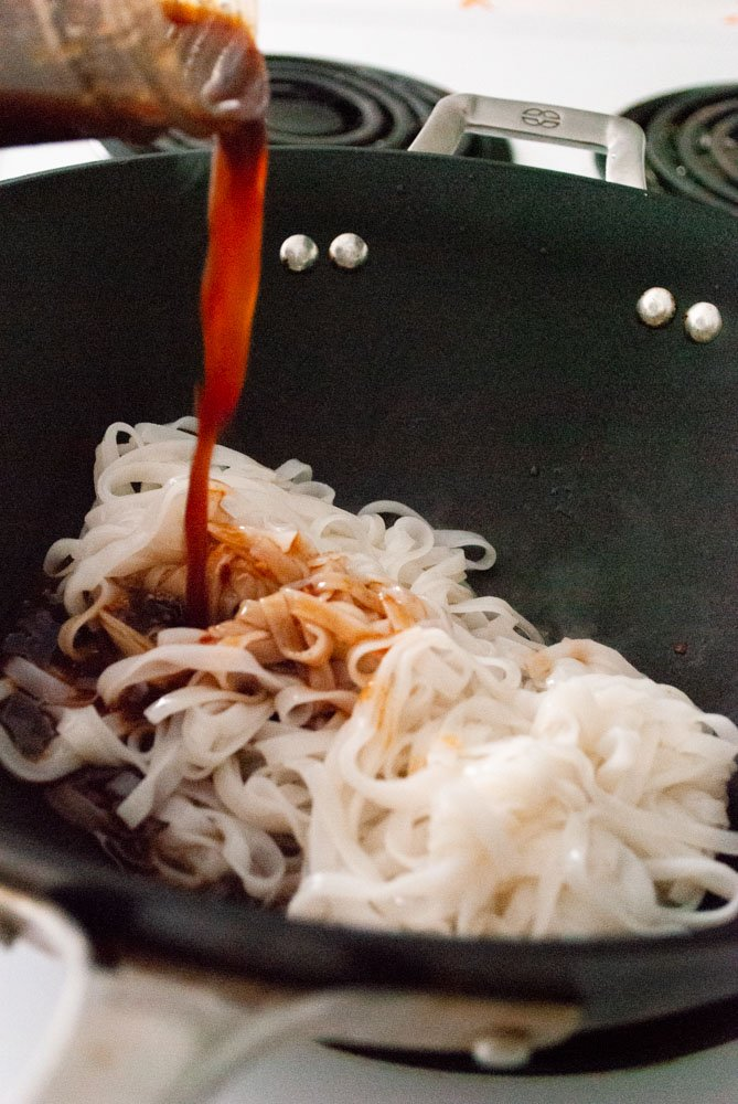 adding the pad Thai sauce to the noodles
