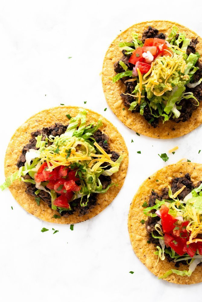 Black bean tostadas toped with lettuce, pico de gallo, guacamole and shredded cheese.