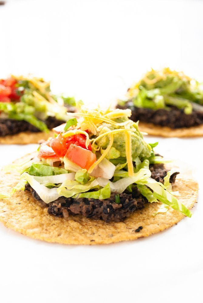 a side angle photo of a black bean tostada piled high with lettuce, guacamoke, pico do gallo and cheese.