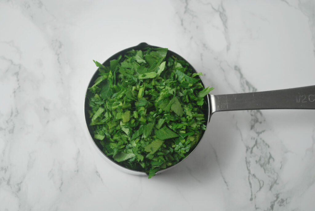 minced parsley in measuring cup