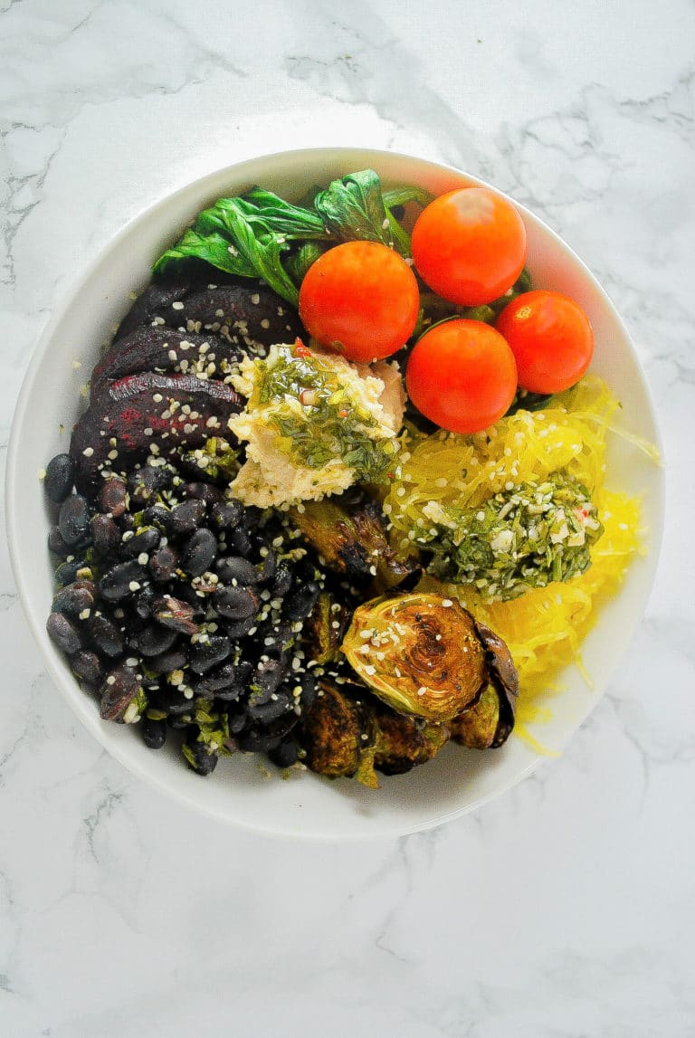 A hearty and filling vegan bowl with black beans, roasted beets and Brussels sprouts, tomatoes, spinach, and spaghetti squash. Topped with hummus and chimichurri. #vegan #bowl #winter #beets #brusselssprouts #roasted #blackbeans
