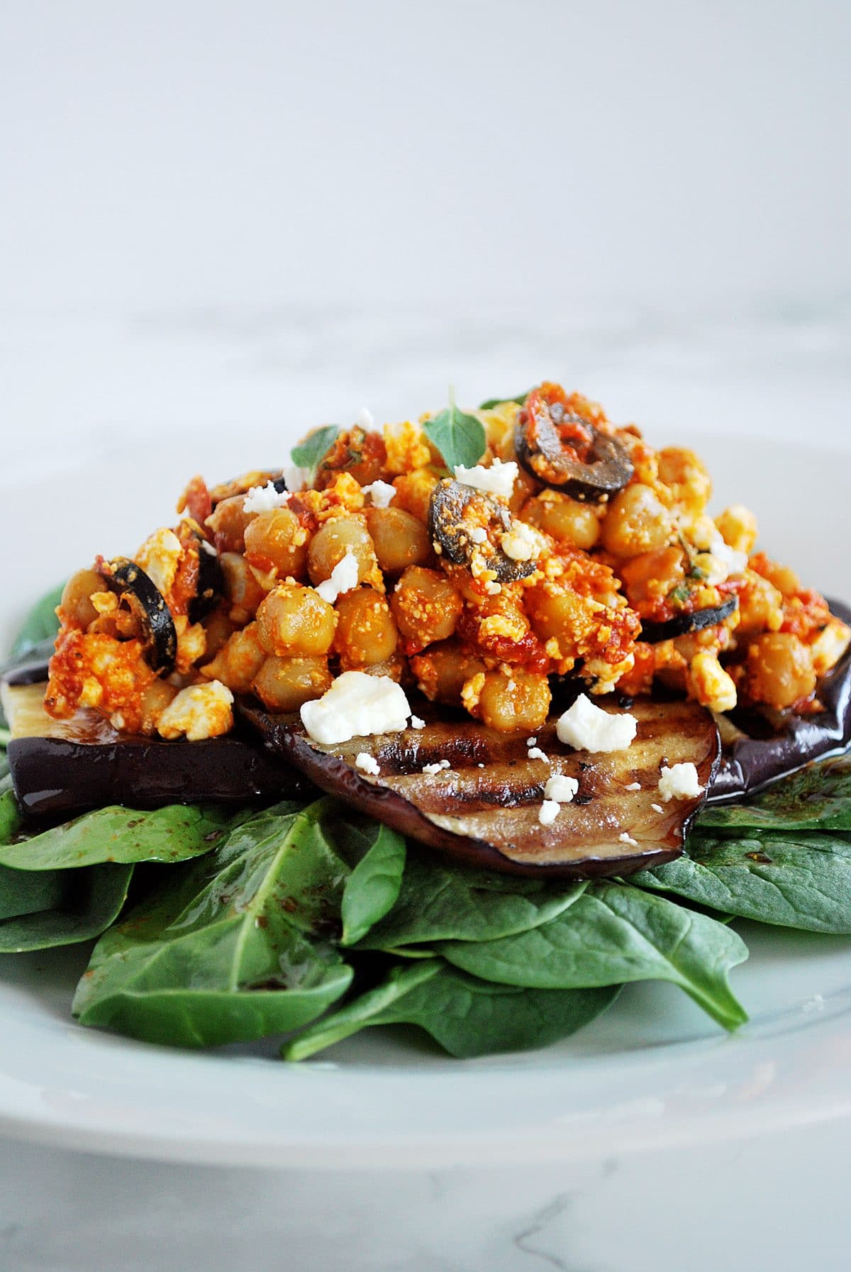 A side view of a plate of chickpea salad with grilled eggplant.