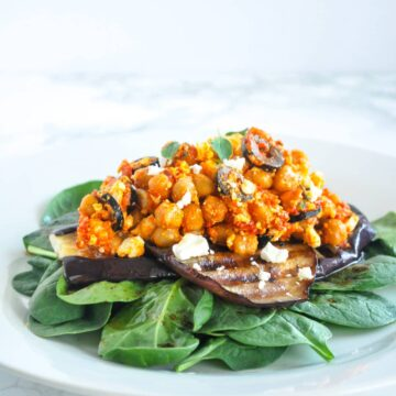 Chickpea salad with grilled eggplant. Roasted red pepper, feta cheese and black olive dressed chickpeas served on grilled eggplant and spinach. Fresh mediterranean flavours. Easy enough for a weeknight, and impressive enough for summer entertaining. #eggplant #chickpeas #salad #summerfood #easy