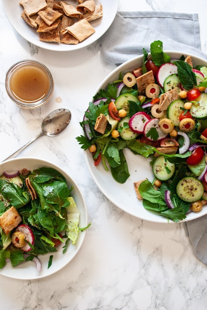 a table with a bowl of fattoush salad alongside a plate of freshly served salad
