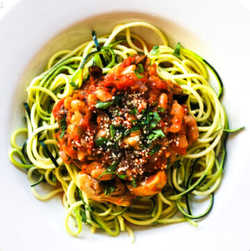 a bowl of vegan puttanesca zoodles with white beans
