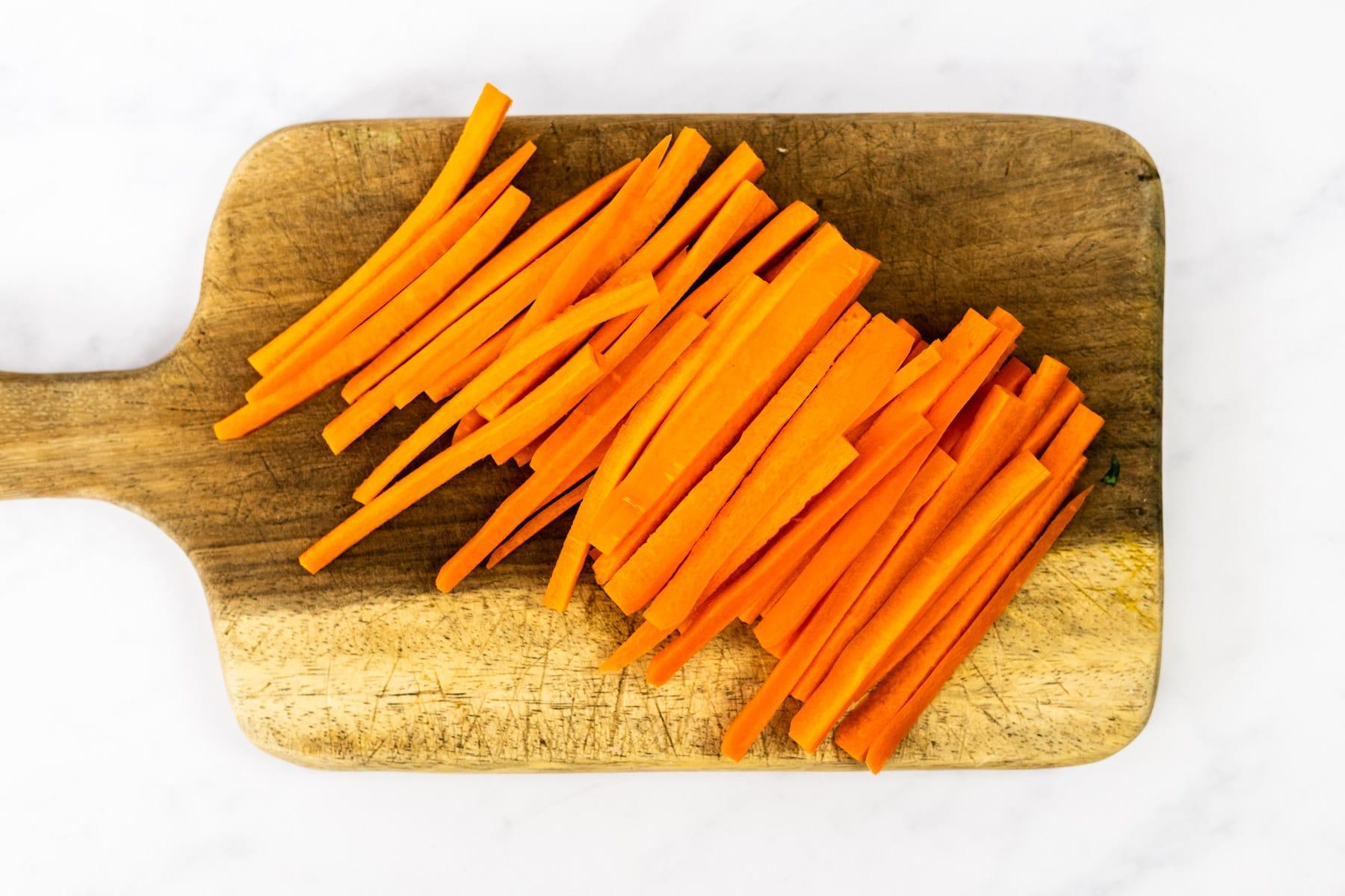 Carrot matchsticks on a cutting board.