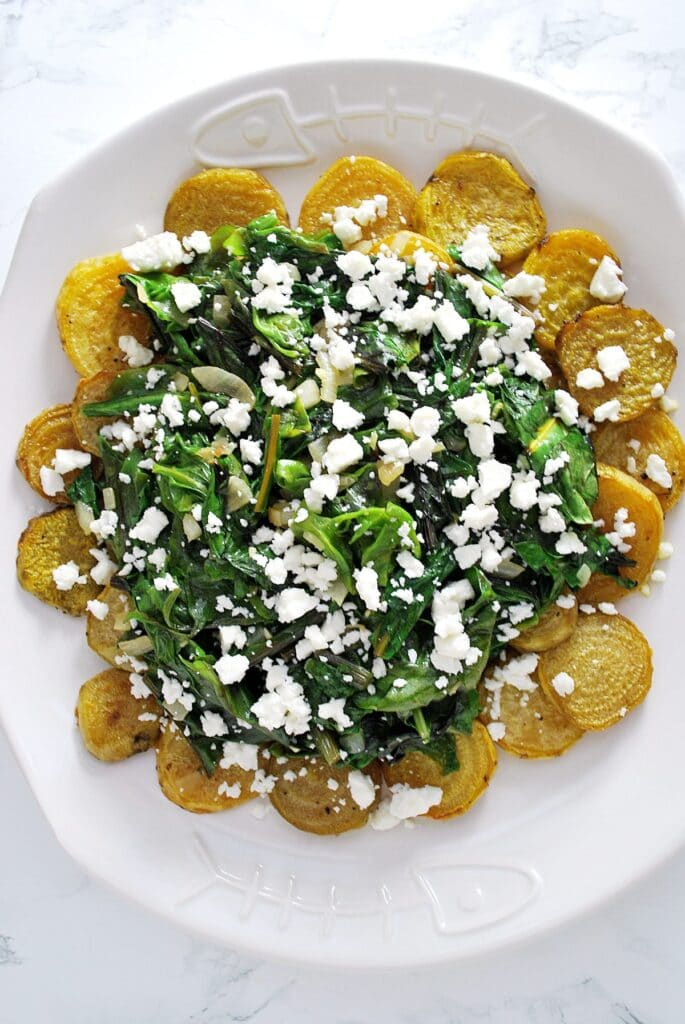 a plate of roasted golden beets with wilted greens and feta