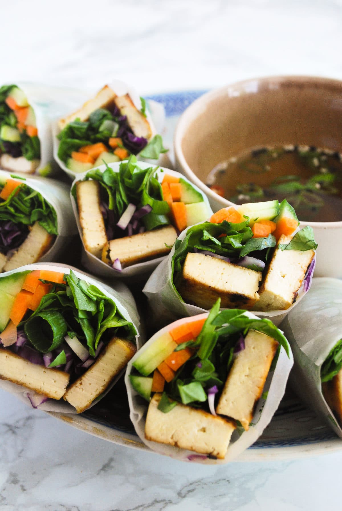 Bahn Mi summer rolls in a bowl next to dipping sauce.