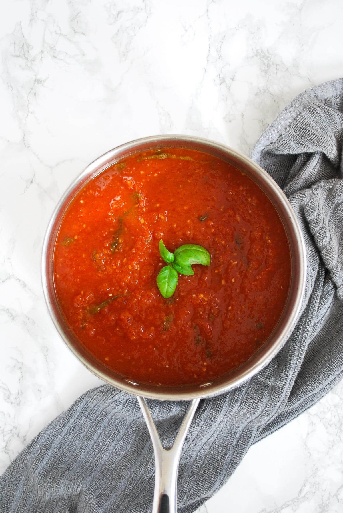 A pot of basic tomato sauce with basil and garlic.