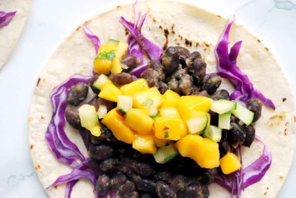 Jerk Black Beans on a corn tortilla topped with mango and cucumber salsa