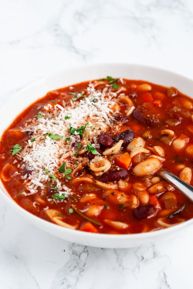 a table set with two bowls of pasta e fagioli