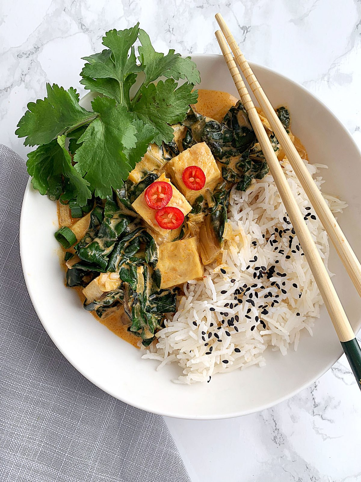 A bowl of red Thai curry tofu and rice with chopsticks resting on the bowl.