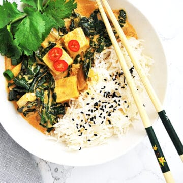 Thai Red curry tofu with swiss chard and rice in a bowl with chopsticks
