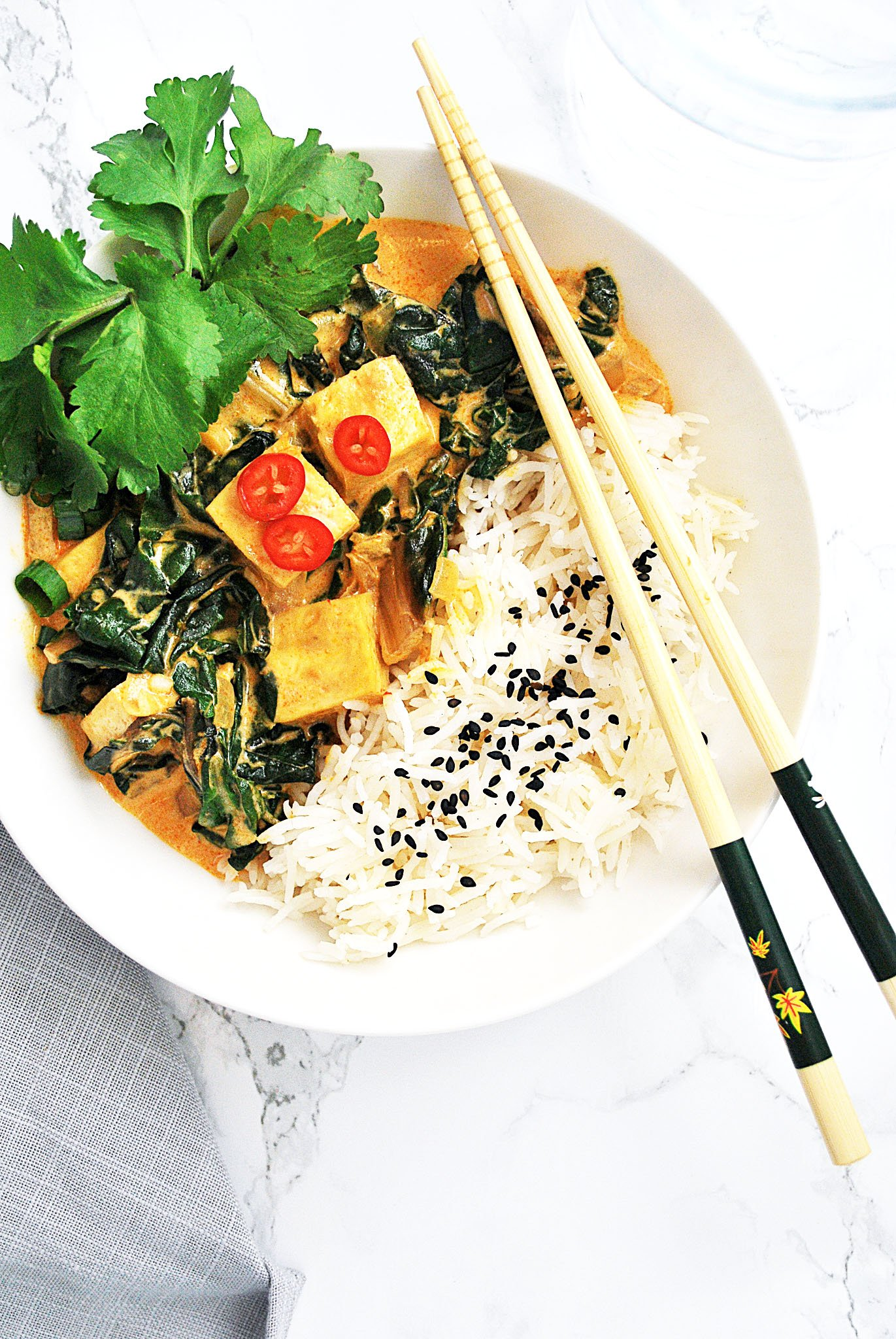 Thai Red curry tofu with Swiss chard and rice in a bowl with chopsticks.