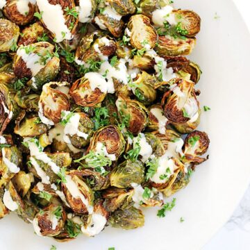 a plate of roasted brussels sprouts drizzled with lemon tahini sauce