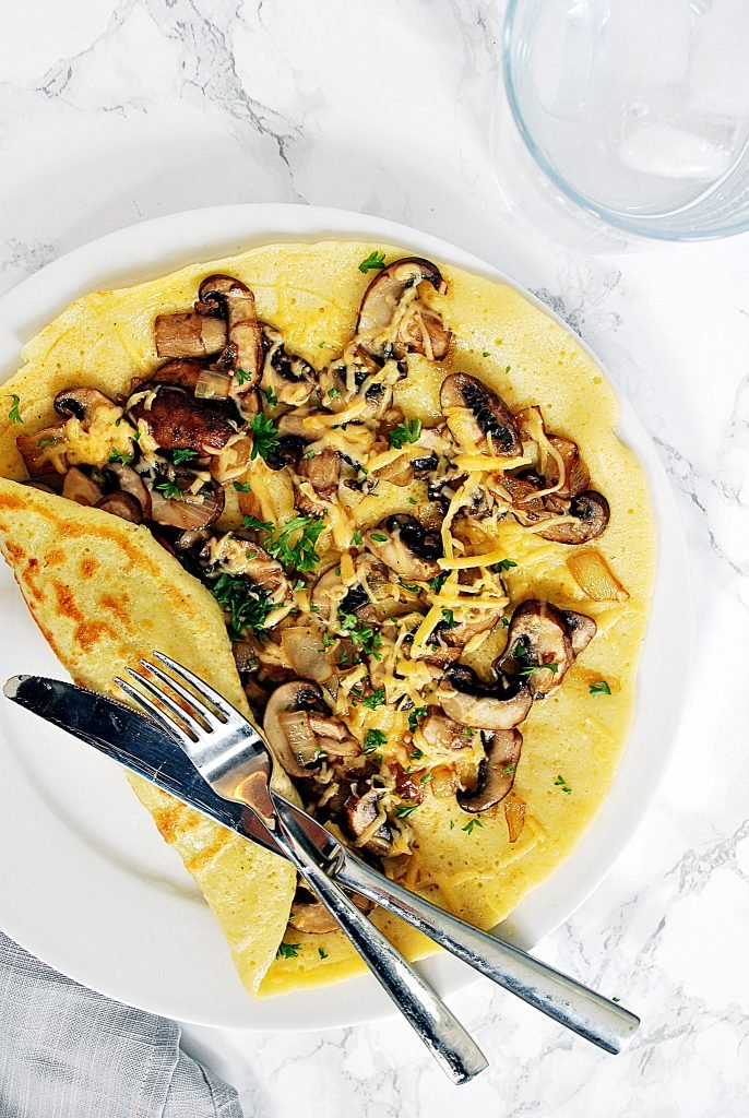 a savoury Dutch pancake with mushrooms and gouda cheese on a plate waiting to be eaten
