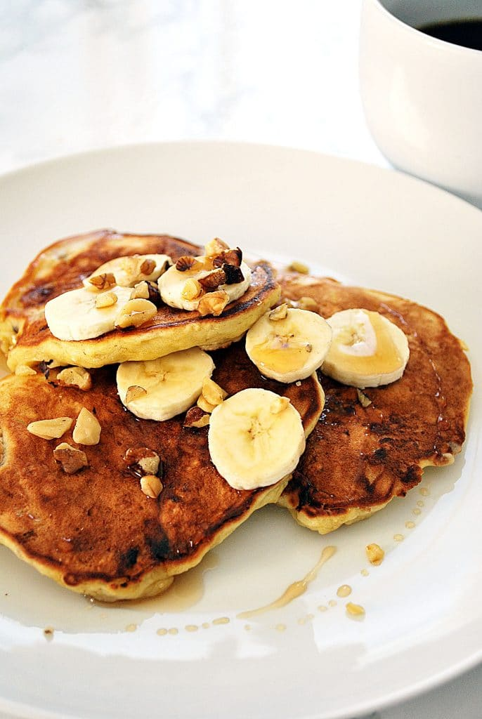 a close up of three banana walnut pancakes on a plate topped with sliced banana, walnut pieces and maple syrup