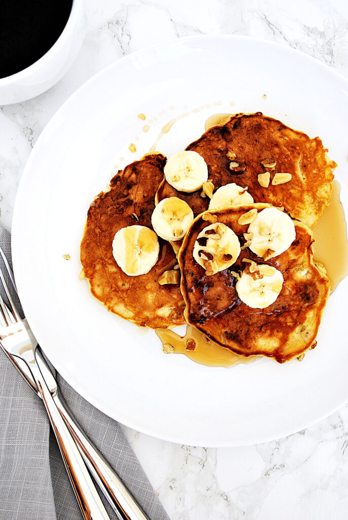 a plate containing three banana walnut pancakes topped with sliced banana, walnuts pieces and maple syrup