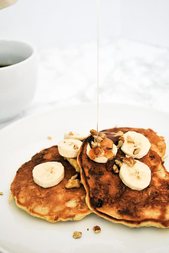 a stack of banana walnut oancakes being drizzled with maple syrup