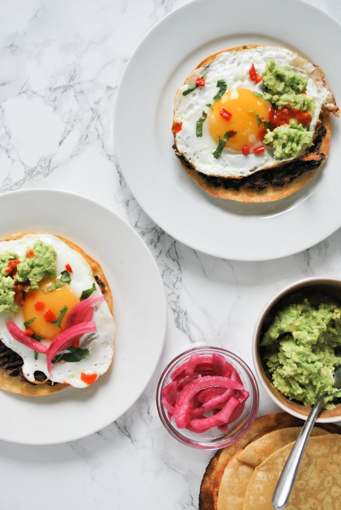two plates with breakfast tostadas surrounded by bowls of toppings