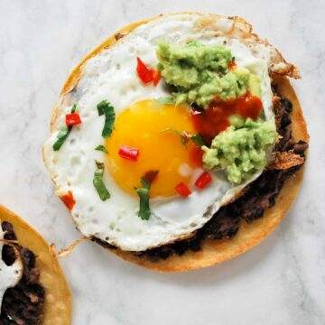 a tostada layered with refried black beans, a fried egg and smashed avocado