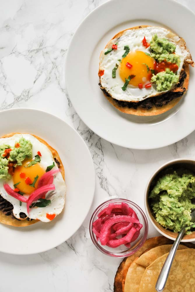 A table set with plates full of easy breakfast tostadas and toppings such as smashed avocado and pickled onions.
