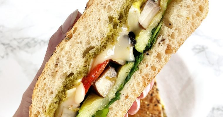 a hand holding up a sandwich with roasted vegetables, brie, and pesto