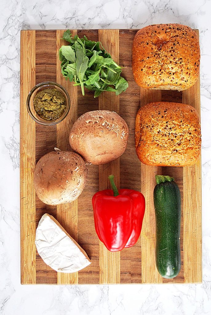 a cutting board with buns, portobello mushrooms, red pepper, zucchini, brie and pesto sitting on it waiting to be turned into roasted vegetable sandwiches