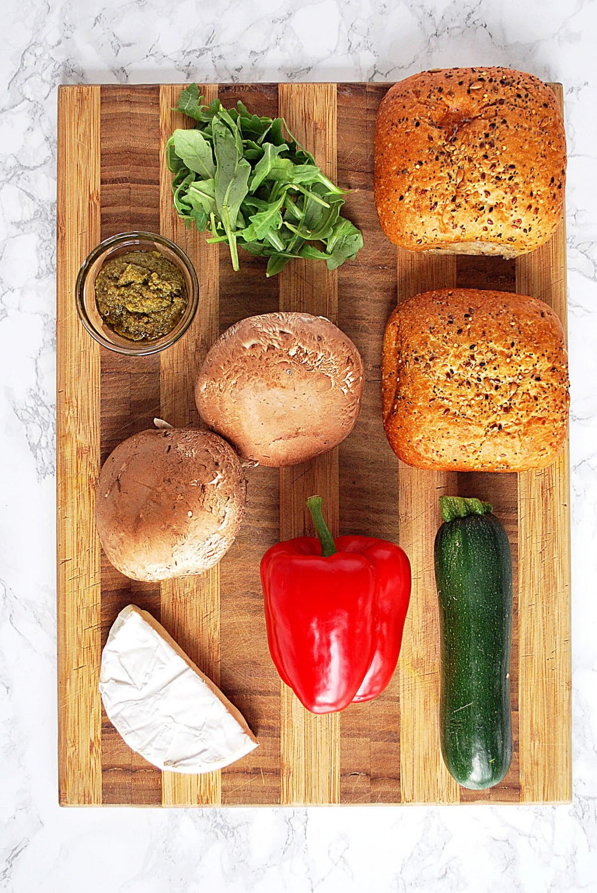A cutting board with roasted vegetable sandwich ingredients on it.