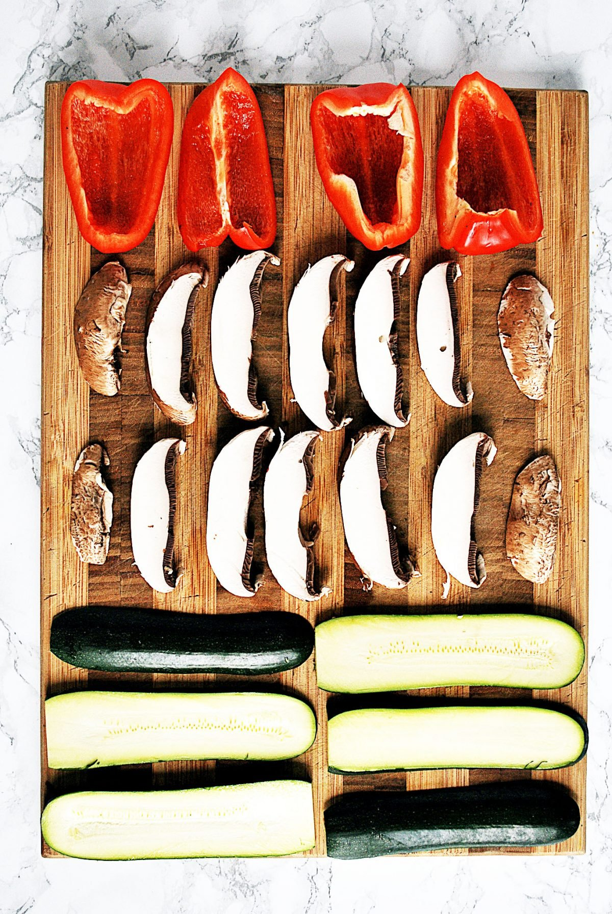 A cutting board with sliced red peppers, portobello mushrooms, and zucchini on it.