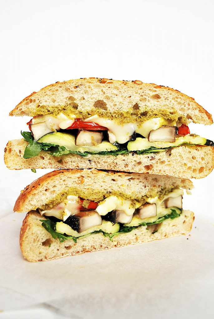 stacked halves of roasted vegetable sandwiches filled with grilled portobello mushrooms, red peppers, zucchini brie and pesto on a ciabatta bun