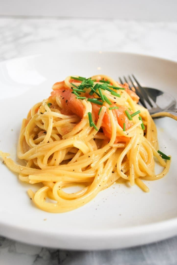A white plate with a portion of smoked salmon carbonara in the middle of it.
