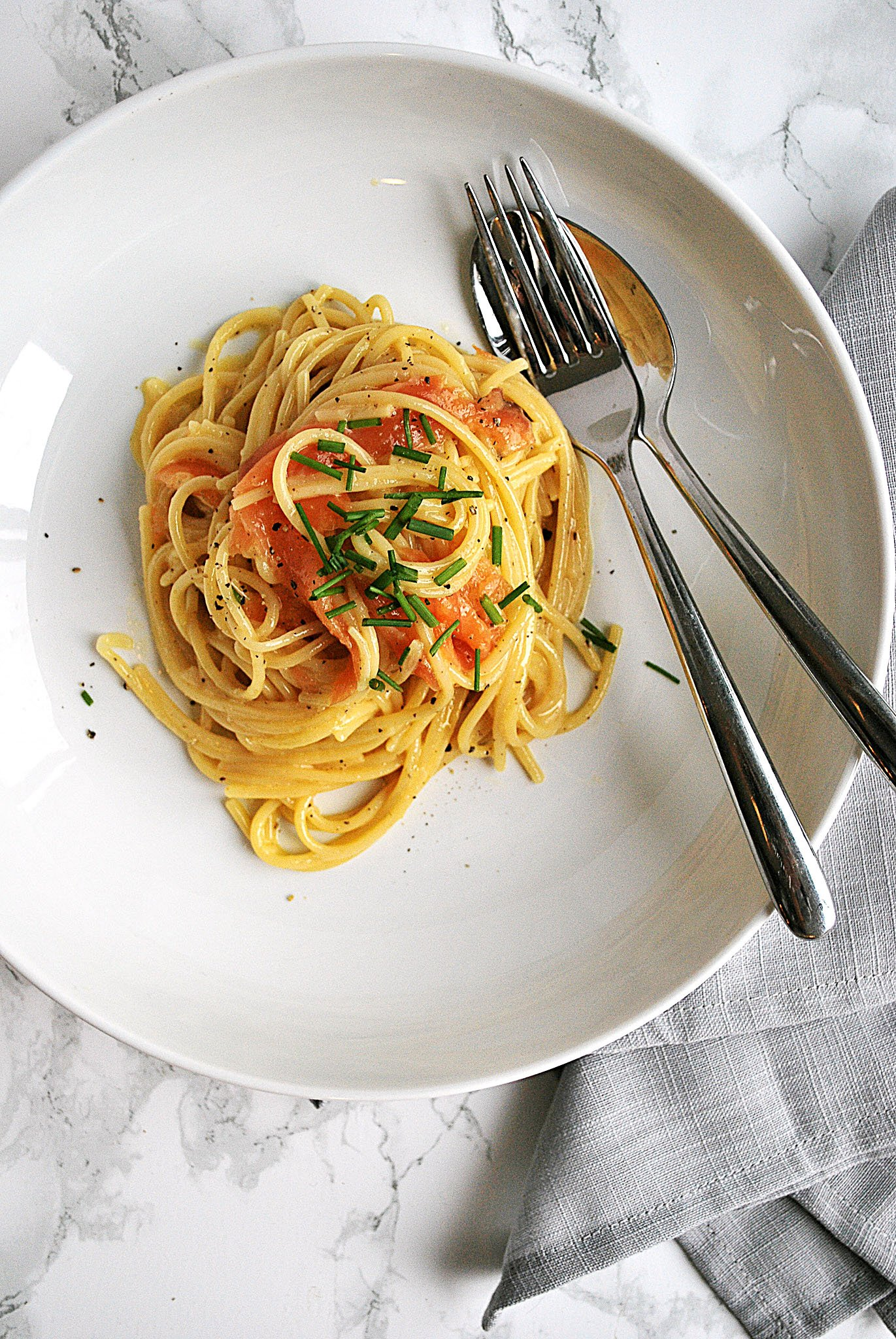 A plate with creamy smoked salmon spaghetti carbonara beside a napkin and cutlery.