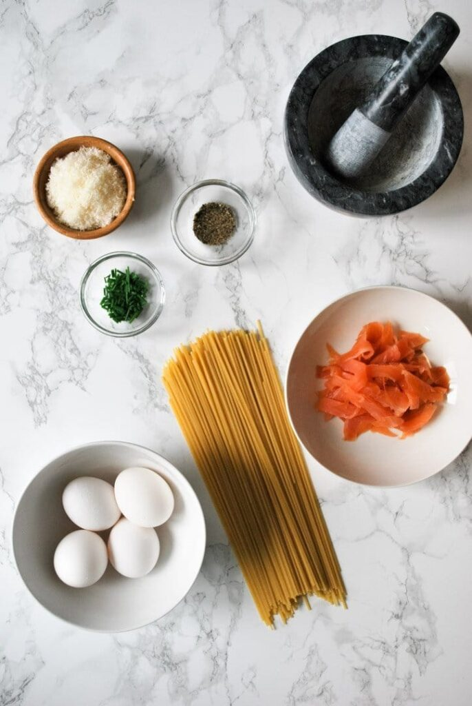 parmesan cheese, smoked salmon, spaghetti, eggs, and pepper - the ingredients for smoked salmon carbonara spread out on the kitchen counter ready to be prepared