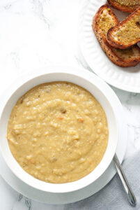 a bowl of split pea soup and a plate of toasted bread on a table