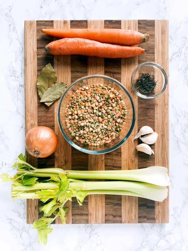 a cutting board topped with the ingredients for making vegan split pea soup