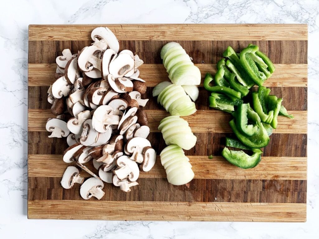 a cutting board topped with sliced mushrooms, onions and green peppers