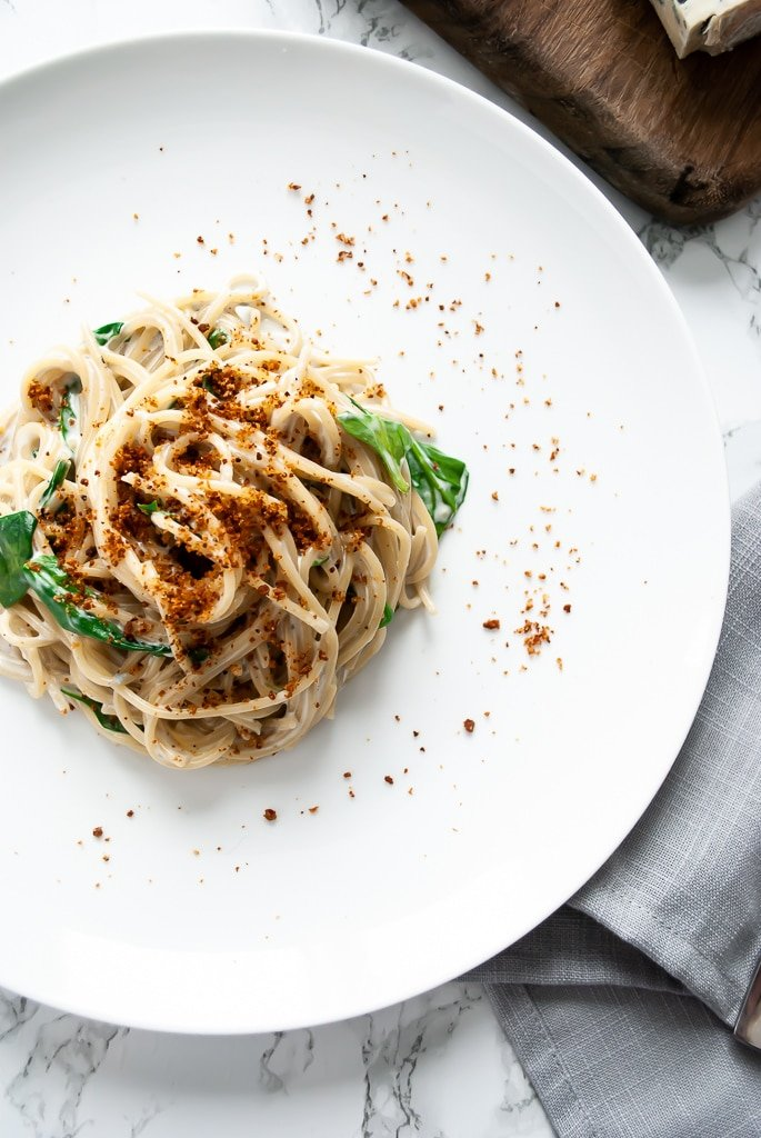A plate of spaghetti gorgonzola with wilted spinach topped with toasted breadcrumbs