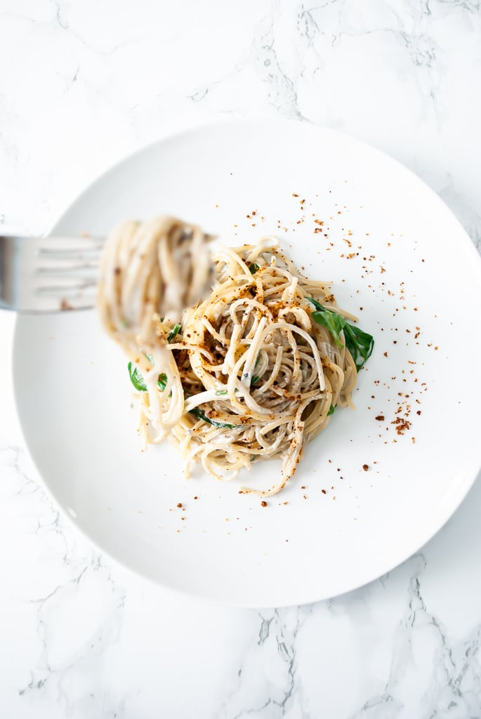 A plate of spaghetti gorgonzola with wilted spinach topped with toasted breadcrumbs.