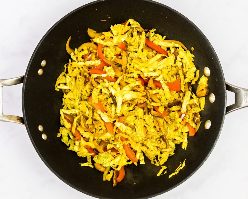 Stir-fried cabbage and veggies in a wok.