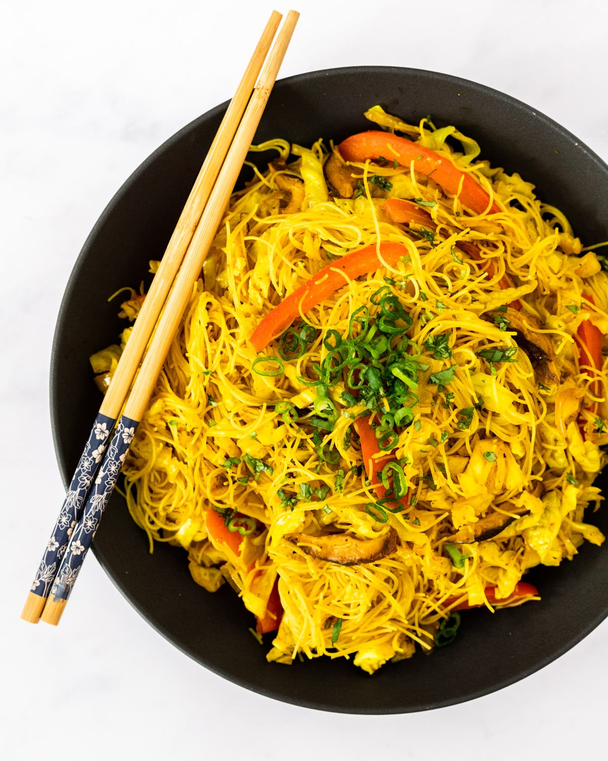A serving bowl filled with vegan Singapore noodles.