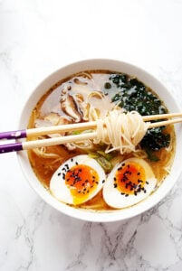 a bowl of vegetarian miso ramen with kale, mushrooms and boiled egg with chopsticks resting on it
