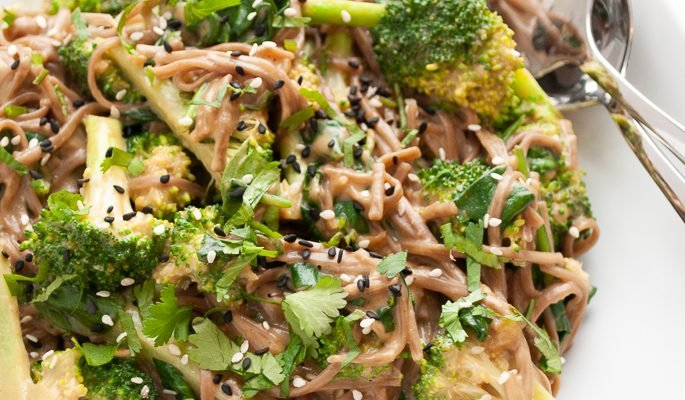 a serving bowl filled with soba noodles tossed with peanut sauce, steamed broccoli and spinach