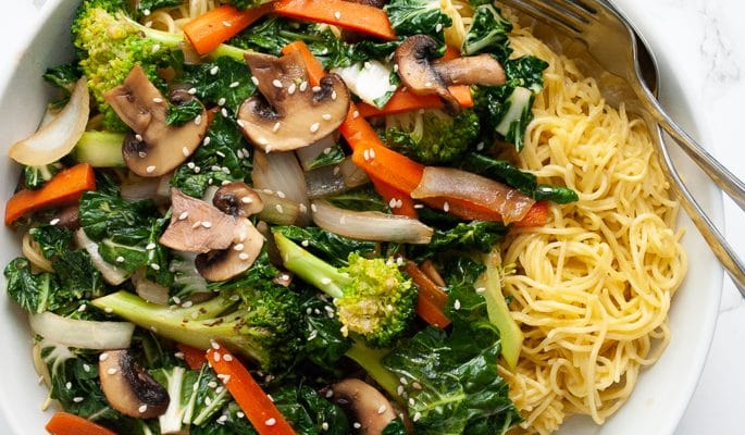 A serving bowl filled with cantonese chow mein noodles topped with stir-fried vegetables