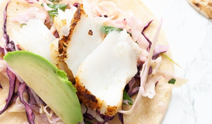 a corn tortilla topped with cilantro lime slaw, flakes of seasoned and seared cod and avocado