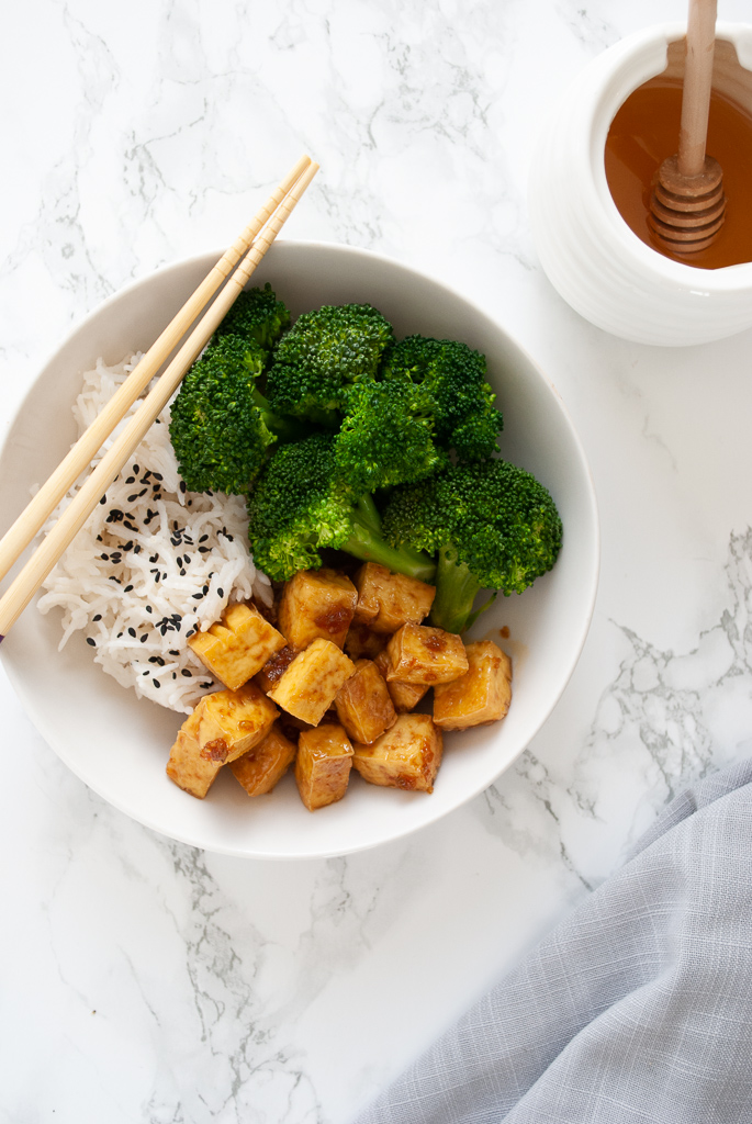 A bowl of oven baked tofu tossed in honey garlic sauce and broccoli and rice.