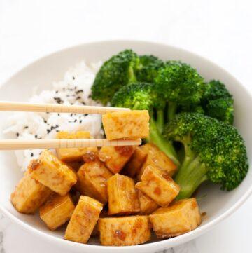 chopsticks holding a piece of honey garlic tofu