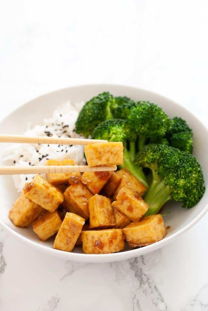 a pair of chopsticks holding a piece of honey garlic tofu with a bowl in the background