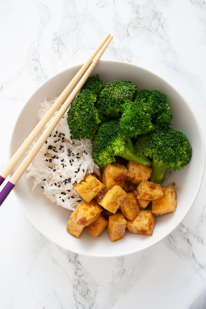 a bowl of tofu cubes tossed in honey garlic sauce served with broccoli and rice